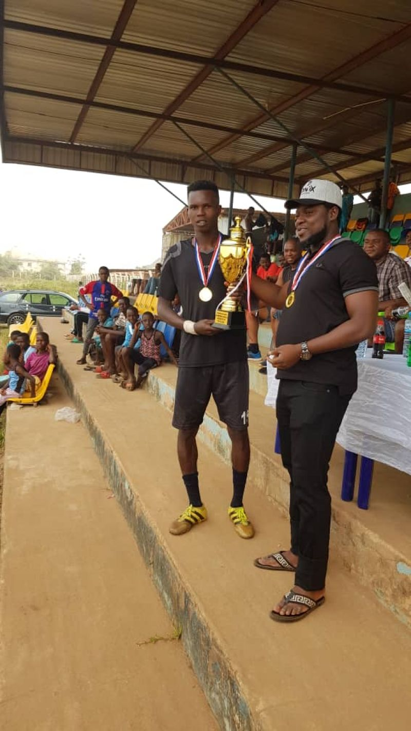 Captain of Ine Stars FC receiving the IB Sports Champions cup last year from the tournament sponsor Benjamin Idahosa (Right).