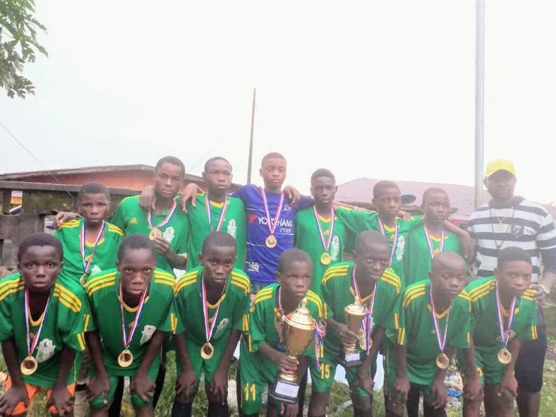 Photo shows Dynamo and coach Ogieriakhi with the gold medals they won in the final of the Egedede N'Okaro football competition at Arinze primary school in Benin city.
